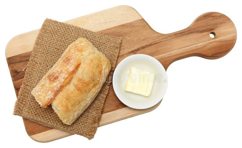Baguette et beurre sur la planche à découper images stock