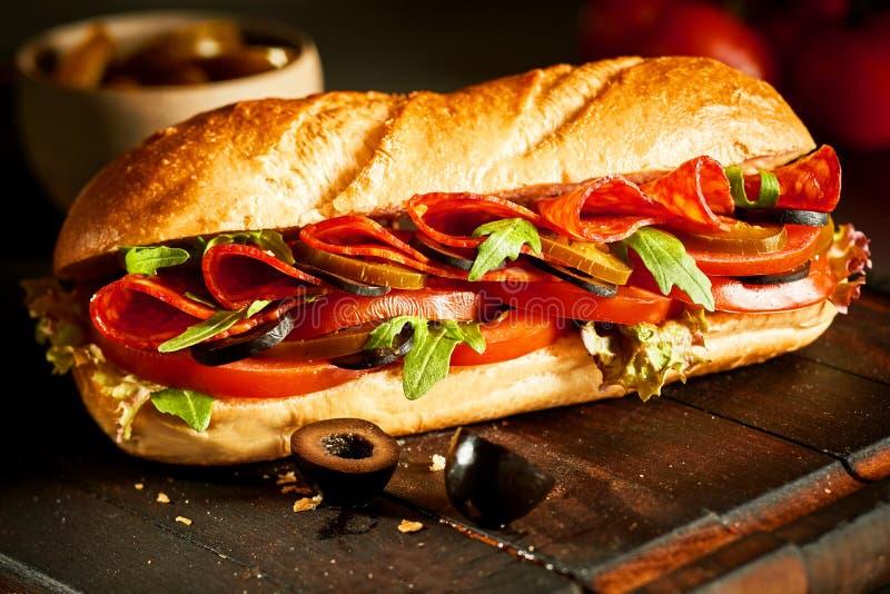 Baguette fraîche croustillante avec le salami et la salade photos stock
