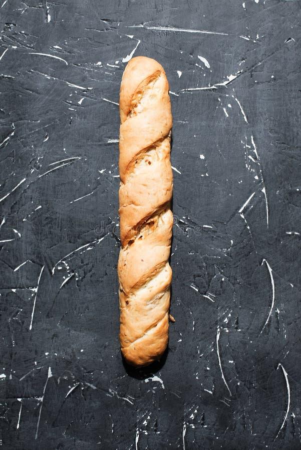 Baguette francês fresco contra um fundo escuro Pão longo da padaria feito da farinha, do trigo e da massa Alimento saudável delic imagem de stock