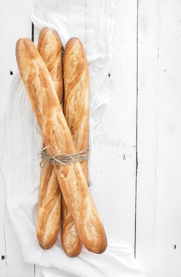 Baguette francesi di recente al forno su di legno bianco fotografie stock