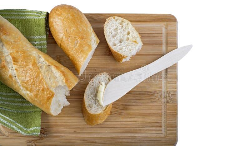 Baguette largo y cuchillo de mantequilla de madera en tabla de cortar de madera imagen de archivo