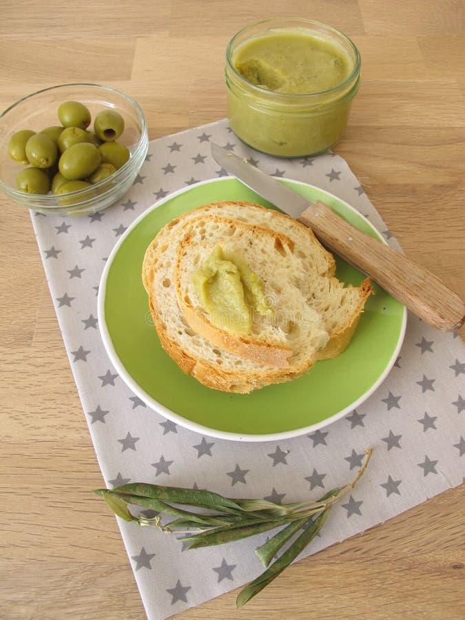 Baguette met groene olijfjam stock fotografie