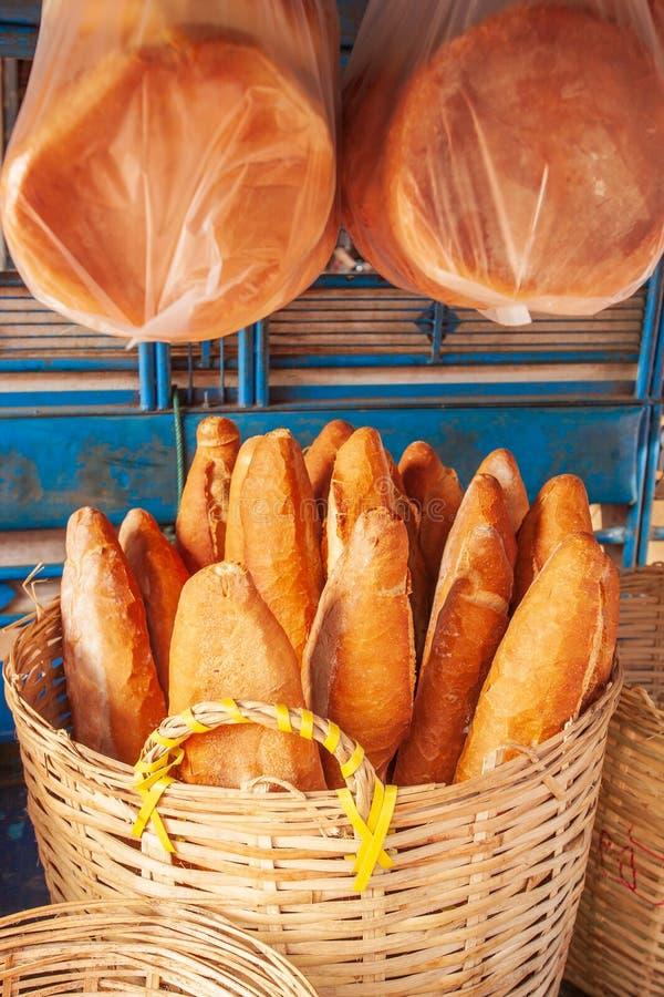 Baguette o pan francés en las cestas de mimbre con el ligh de la mañana imagen de archivo