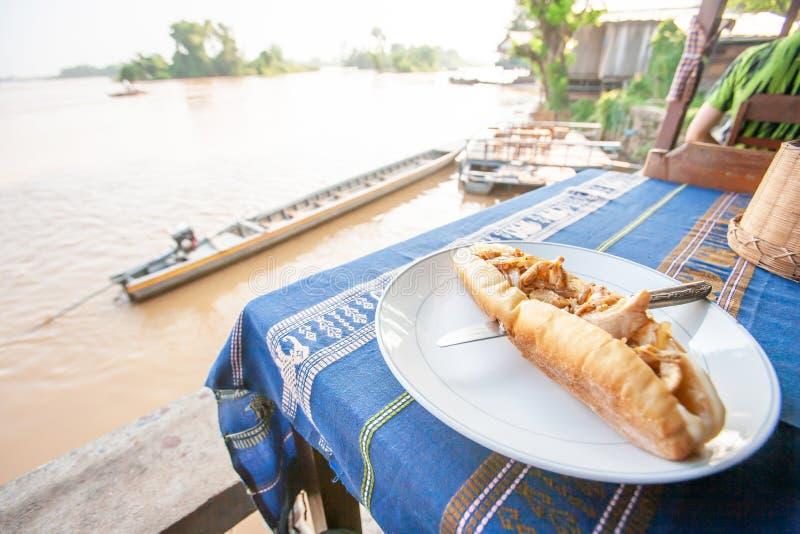Baguette op Laotiaans traditioneel tafelkleed met toneelmening over de Mekong Rivier stock foto