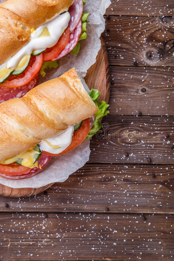 Baguette with salami , fresh vegetables royalty free stock photo