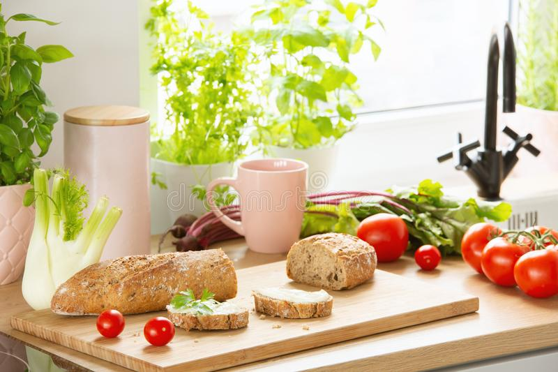 Baguette, tomatoes, pink mug, celery and herbs on a countertop in a kitchen interior. Real photo royalty free stock photos