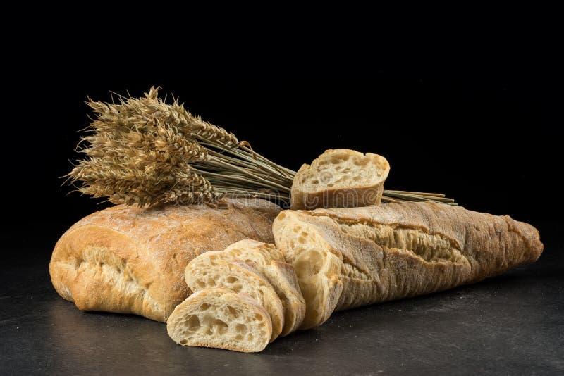 Baguette y ciabatta, rebanadas del pan en la tabla de madera oscura Trigo y panes mezclados frescos en fondo negro fotos de archivo libres de regalías