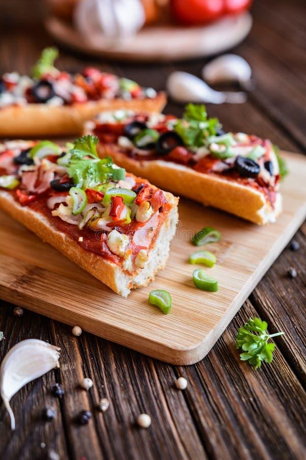 Baguettepizza met bacon, salami, kaas en groente stock afbeeldingen
