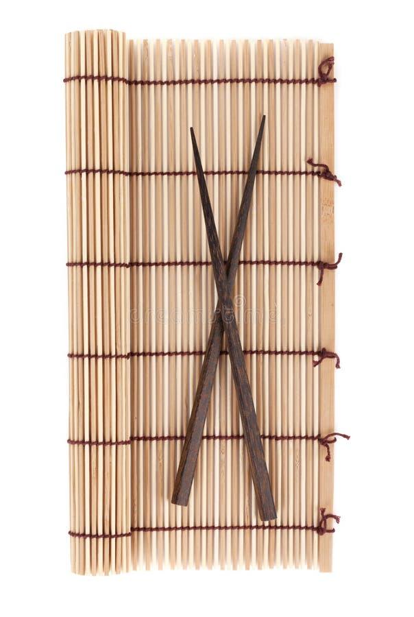 Baguettes au-dessus du tapis en bambou images libres de droits