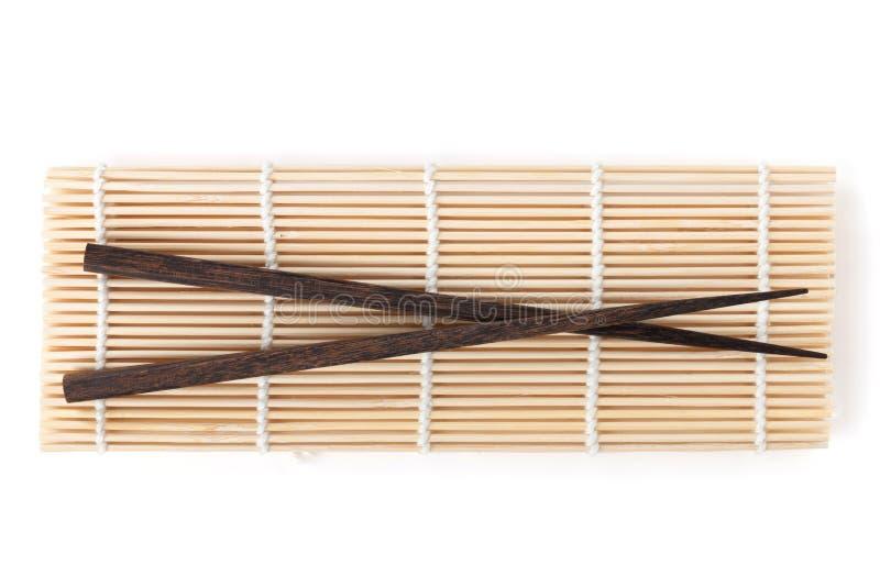 Baguettes au-dessus du tapis en bambou image libre de droits