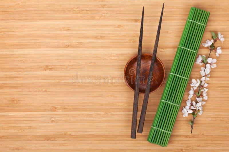 Baguettes, branche de Sakura et tapis de bambou photographie stock