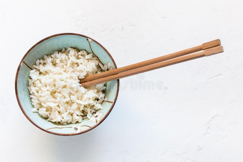 Baguettes dans la cuvette avec du riz bouilli sur le blanc photo stock