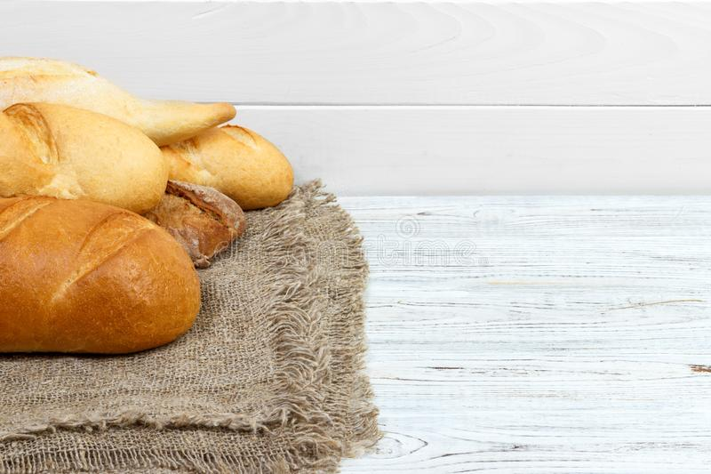 Baguettes de pain sur le blanc rustique peint en bois photos stock