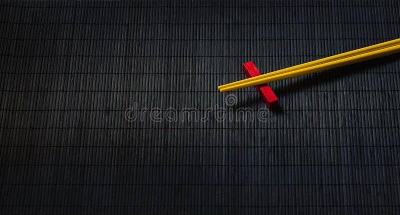 Baguettes de sushi sur le tapis de paille de bambou noir photos libres de droits