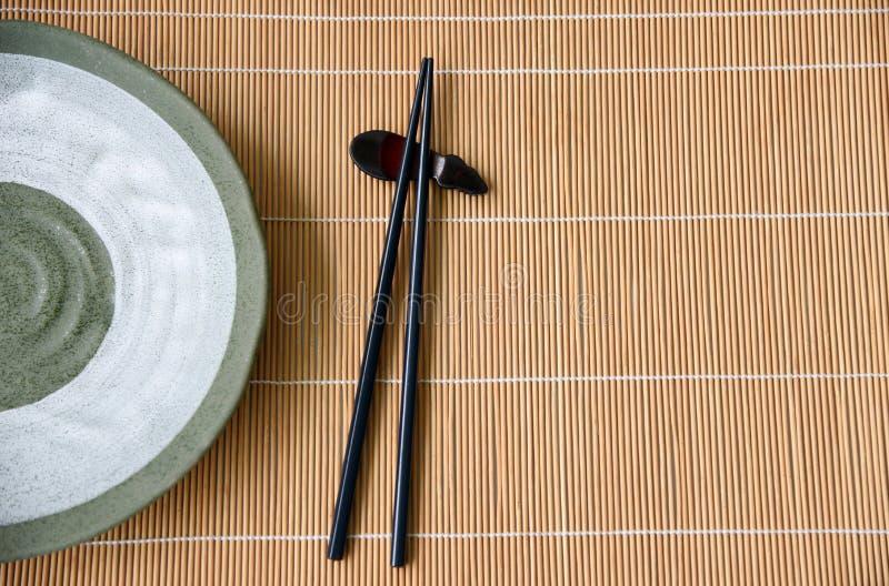 Baguettes en bois et style en céramique d'oriental de vert de plat photographie stock libre de droits
