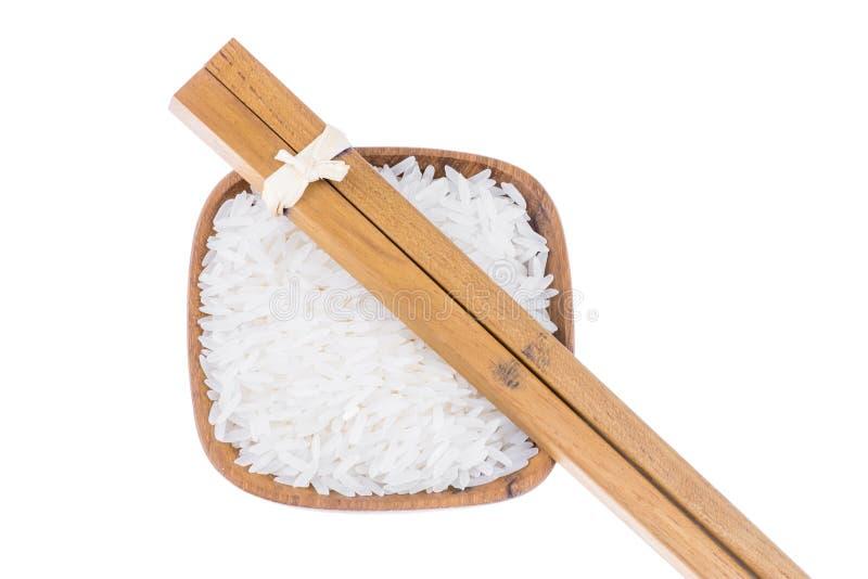 Baguettes en bois naturelles avec du riz dans la petite cuvette en bois photographie stock libre de droits