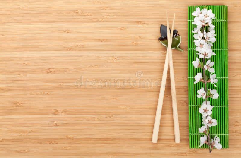 Baguettes et branche de Sakura au-dessus du tapis en bambou images stock