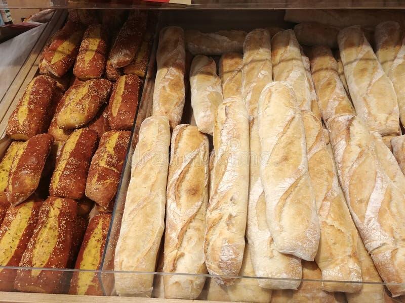 Baguettes françaises croquantes fraîchement cuites au four chaudes et pain de fantaisie à l'étagère de devanture de magasin images libres de droits