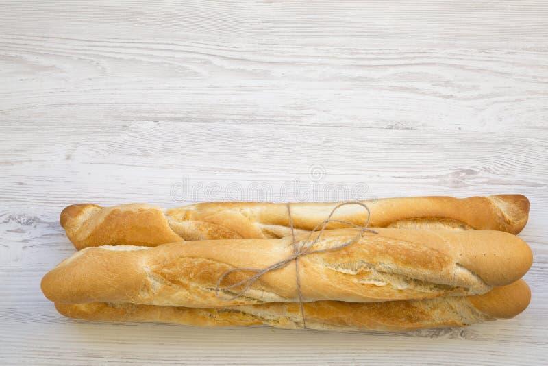 Baguettes franceses frescos no fundo de madeira branco, vista superior foto de stock