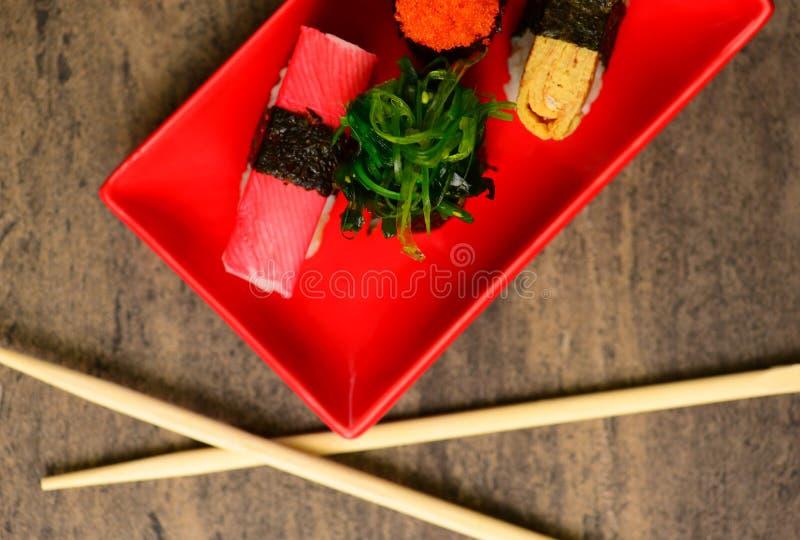 Baguettes près des sushi avec les poissons et l'algue photo libre de droits