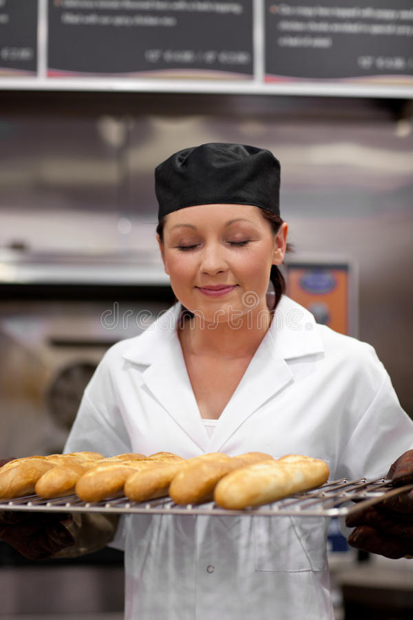 Baguettes sentantes de jeune boulanger mignon photos libres de droits
