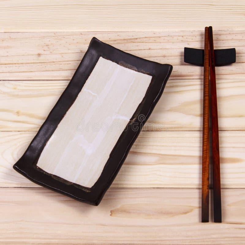Baguettes vides de plat et de sushi sur la table en bois image libre de droits