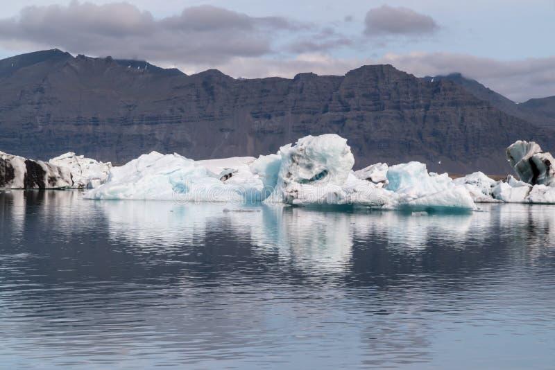Bahía de la laguna del glaciar de Jokulsarlon con los icebergs azules que flotan en el agua inmóvil con reflexiones, Islandia imagenes de archivo