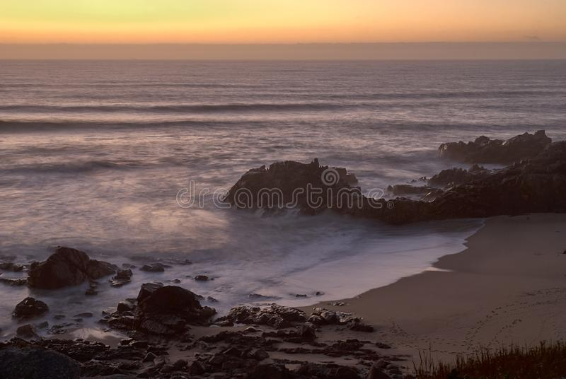 Bahía de la playa con la luz anaranjada de la puesta del sol fotos de archivo