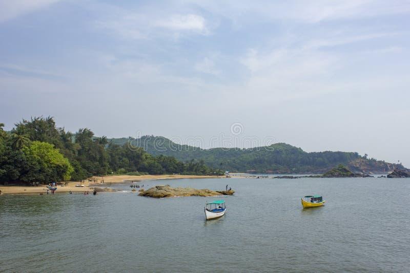 Bahía del mar con los barcos de placer en el agua, contra la perspectiva del bosque verde en la reclinación de la playa arenosa y imagen de archivo
