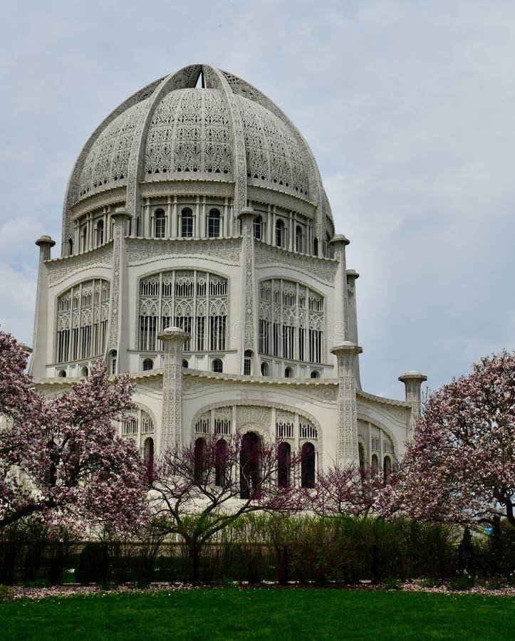 Baha'i i-hus av dyrkan över att blomstra magnoliaträd arkivbilder