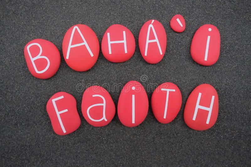 Baha i Faith, religion name composed with red colored stones over black sand. Baha i Faith is a religion teaching the essential worth of all religions, and the stock images