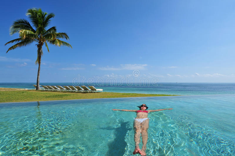 Bahamas. Woman swimming in the infinity pool under the sun in beautiful tropical beach resort in The Bahamas stock images