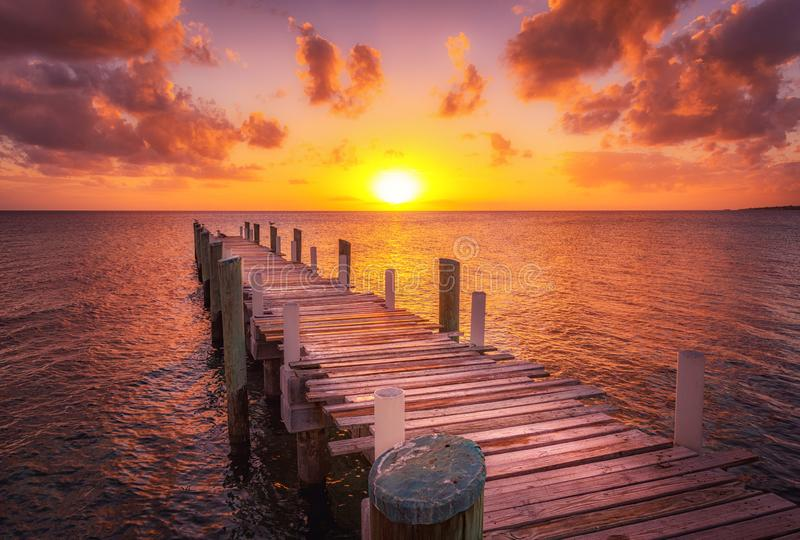 Bahamas dock sunset ocean. Dock during caribbean sunset, beautiful magenta colors and perspective of this boat dock and fishing dock in Eleuthera island, Bahamas royalty free stock photography