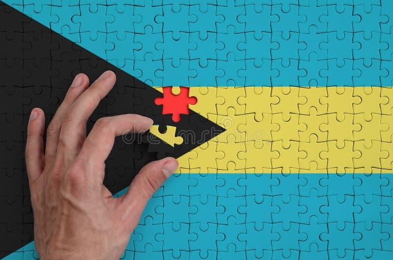 Bahamas señalan por medio de una bandera se representan en un rompecabezas, que la mano del ` s del hombre termina para doblar fotos de archivo libres de regalías