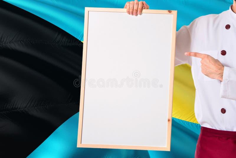 Bahamiaanse Chef-kok die leeg whiteboardmenu op de vlagachtergrond van de Bahamas houden Kok die eenvormige richtende ruimte voor royalty-vrije stock afbeeldingen