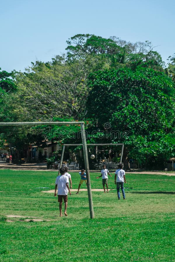 BAHIA, BRAZIL - June 27, 2019: Group of local children playing soccer in a humble grass field with bent goals in the royalty free stock image