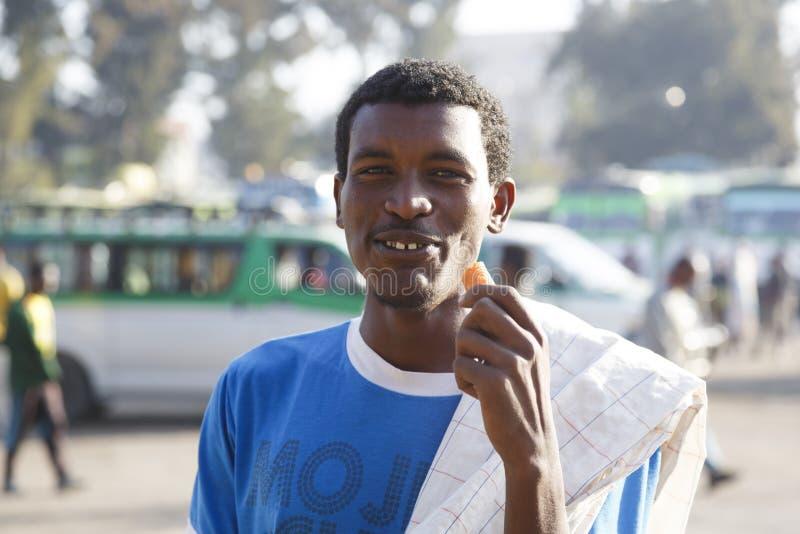Bahir Dar, Ethiopië, 15 Februari 2015: Een jonge Ethiopiër bevindt zich in backlight en eet een wortel stock afbeelding