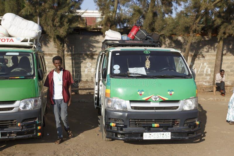 Bahir Dar, Ethiopië, 15 Februari 2015: Een jonge Ethiopiër wacht op een vertrek bij een busstation naast een minibus royalty-vrije stock foto's