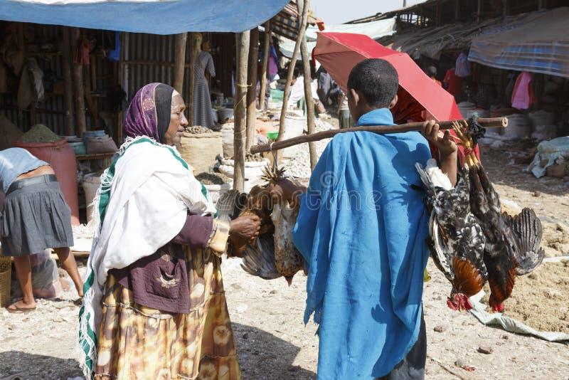 Bahir Dar, Ethiopië, 14 Februari 2015: Een vrouw koopt op een markt een kip van een handelaar stock foto