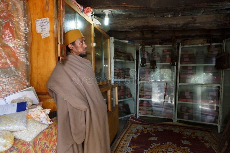 Bahir Dar, Etiopía, el 22 de enero de 2015: Un monje protege los libros ortodoxos en un monasterio en una península en el lago Ta fotos de archivo
