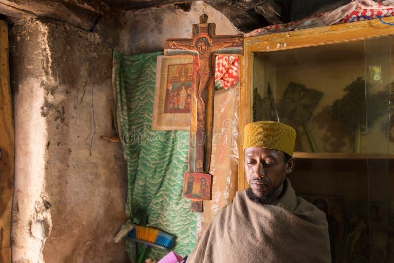 Bahir Dar, Etiopía, el 22 de enero de 2015: Un monje protege los libros ortodoxos en un monasterio en una península en el lago Ta imágenes de archivo libres de regalías