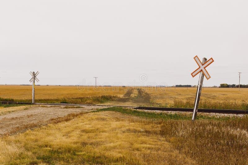 Bahnübergang eine Schotterstraße mit ikonenhaften Überfahrtzeichen stockbilder