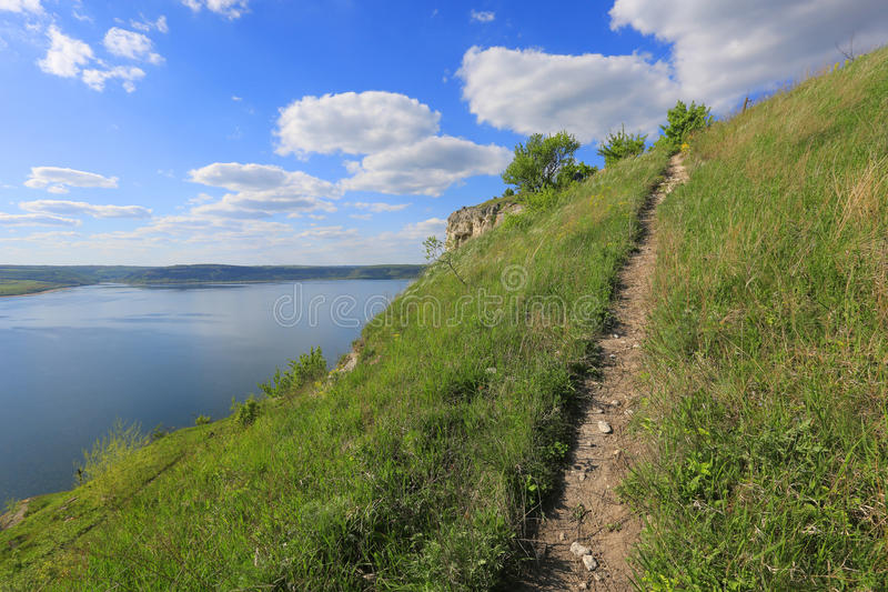 Bahn über Hügel nahe großem See lizenzfreie stockfotografie