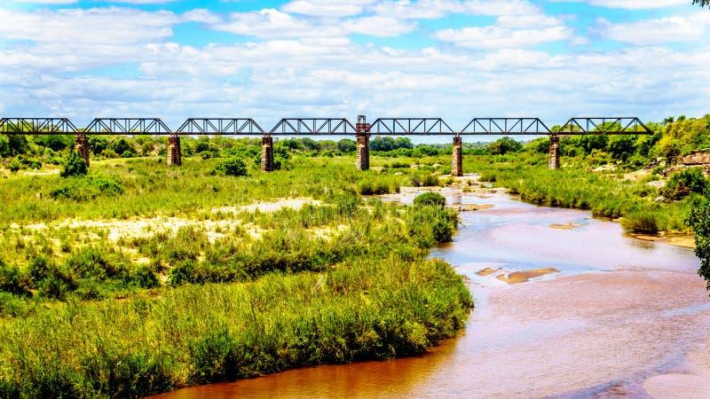 Bahnfachwerkbrücke über Sabie River am Skukuza-Rest-Lager in Nationalpark Kruger lizenzfreies stockfoto