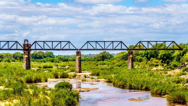 Bahnfachwerkbrücke über Sabie River am Skukuza-Rest-Lager in Nationalpark Kruger stockfotografie
