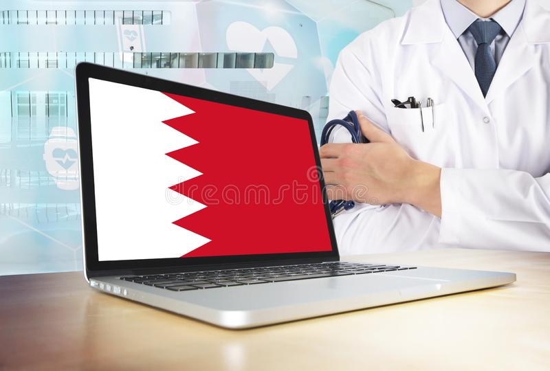 Bahrain healthcare system in tech theme. Bahraini flag on computer screen. Doctor standing with stethoscope in hospital. Cryptocurrency and Blockchain concept stock photography