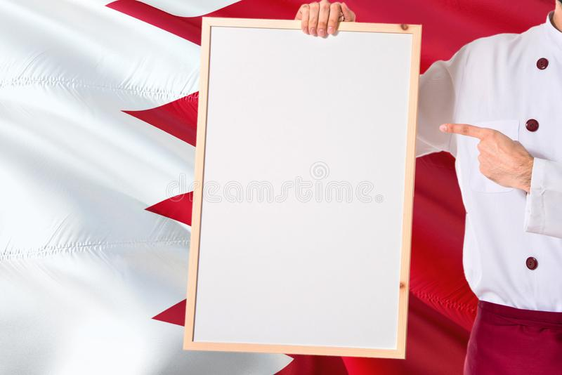 Bahreinse Chef-kok die leeg whiteboardmenu op de vlagachtergrond van Bahrein houden Kok die eenvormige richtende ruimte voor teks stock afbeeldingen