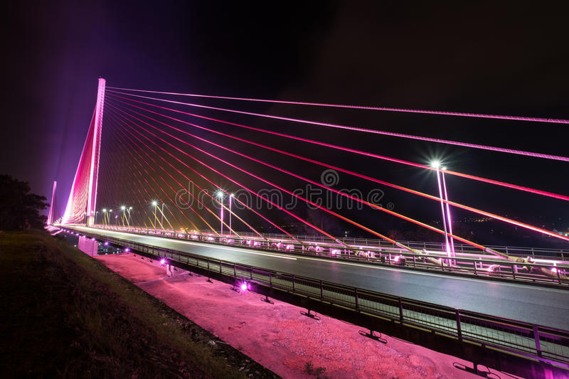 The Bai Chay Bridge in Ha Long Vietnam lit up with colorful lighting at night. stock photography