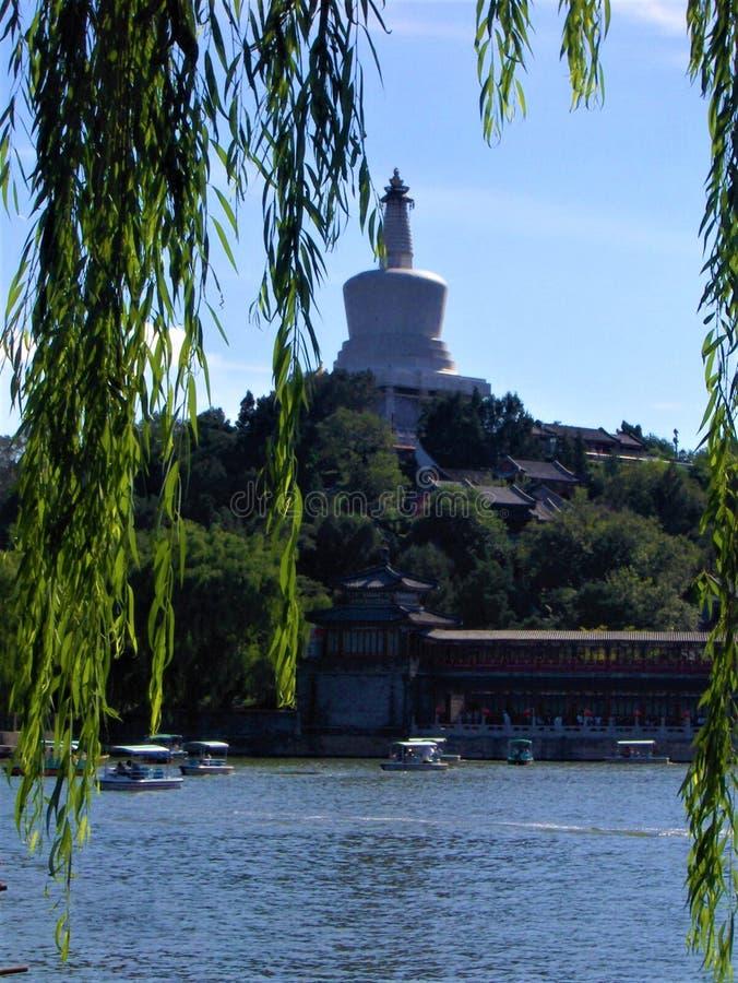 Bai Ta White Pagoda no parque de Beihai, no dia ensolarado, nos barcos e no salgueiro chorando na cidade do Pequim, China imagens de stock
