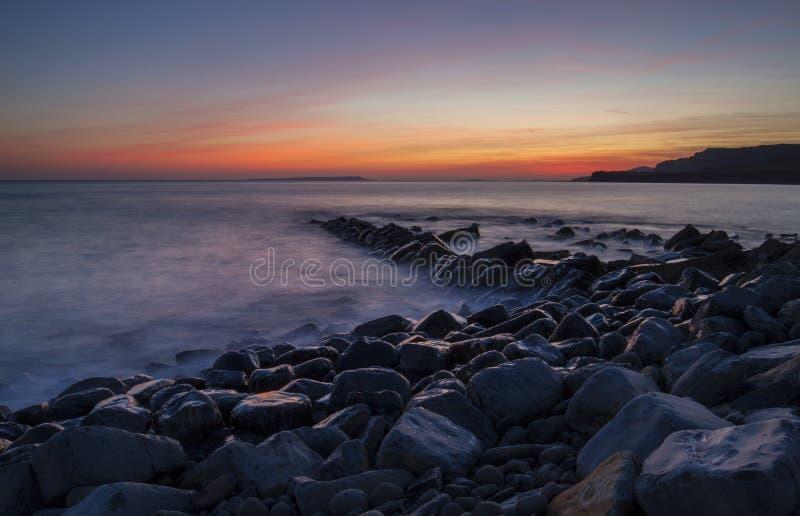 Baia di Kimmeridge con le rocce bagnate ed il tramonto immagine stock libera da diritti
